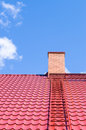 Brick chimney on red roof with metal ladder Royalty Free Stock Photo