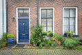 Brick Facade of Old Dutch House with flowers in pots Royalty Free Stock Photo