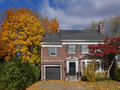 Brick house with maple tree and fall colors Royalty Free Stock Photo