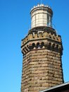 The brick lighthouse is topped by its large light and guides mariners safely into harbor Royalty Free Stock Images