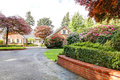 Brick red house with English garden and white window shutters and driveway. Royalty Free Stock Photo