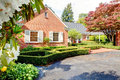 Brick red house with English garden and white window shutters. Royalty Free Stock Photo