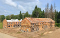 Brick site under construction with wooden roof unfinished houses of Royalty Free Stock Images