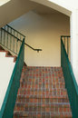 Brick stairway in florida looking up at a stair way with green railings Royalty Free Stock Image