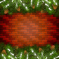 Brick wall background with Christmas fir tree branches and snow Royalty Free Stock Photo