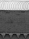 Brick wall with barbed wire on top Royalty Free Stock Photo