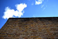 Brick wall set against blue sky with clouds Royalty Free Stock Photo