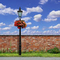 Brick wall with street light a red an old and blue sky Stock Images