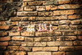 Brick wall thai temple with blessing doll filter with a retro styl Royalty Free Stock Photo