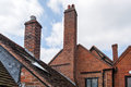 Bricked chimneys above the roofs Stock Photos