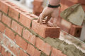 Bricklayer laying bricks setting by plumb line Royalty Free Stock Photography