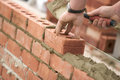Bricklayer laying bricks setting by plumb line Stock Photos