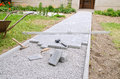 Bricklayer places concrete paving stone blocks for building up a patio, using hammer and spirit level Royalty Free Stock Photo