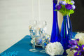 Bridal bouquet of blue iris white tulips glasses and bottles Royalty Free Stock Photo