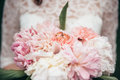 A bridal bouquet of cream peonies is taken by the bride Royalty Free Stock Photo