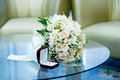 Bridal bouquet and wedding rings on a glass table Stock Image