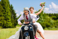 Bridal pair driving motor scooter wearing gown and suit Royalty Free Stock Photo