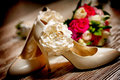 Bridal shoes and rings against wedding bouquet flowers Royalty Free Stock Photo