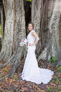 Bride by banyan tree a beautiful smiling standing under a holding bouquet Stock Images