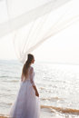 Bride on the beach with flying veil Stock Photo