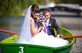 Bride in boat caucasian groom rowing a while is holding flowers Stock Images
