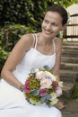 Bride with bouquet of roses smiling young outdoors Stock Photos