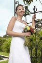 Bride With Bouquet Standing By Gate Royalty Free Stock Photography
