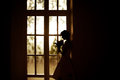 Bride with a bouquet of standing at the window Royalty Free Stock Photo