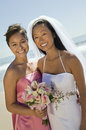 Bride and bridesmaid with flower bouquet smiling on beach portrait of beautiful young Stock Images