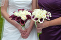 Bride and bridesmaid with wedding bouquets holding purple white Royalty Free Stock Photo