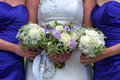 Bride and bridesmaids with wedding bouquets of purple white roses Stock Photos