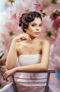 The bride brunette sitting on a chair background of flowers Royalty Free Stock Photo