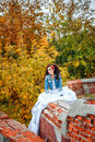 Bride in city park beautiful wedding dress and denim jacket autumn Royalty Free Stock Photo