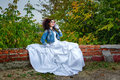 Bride in city park beautiful wedding dress and denim jacket autumn Stock Photo