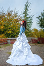 Bride in city park beautiful wedding dress and denim jacket autumn Royalty Free Stock Images