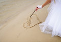 Bride drawing heart on the sand Royalty Free Stock Photo