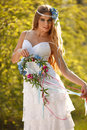 Bride dressed hippie style stands outdoors spring park Stock Photos