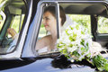 Bride driving car smiling the while holding bunch of flowers Royalty Free Stock Images