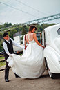Bride entering classic car and driver holding dress Royalty Free Stock Photo