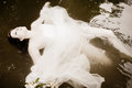 Bride floating in the water Royalty Free Stock Photos