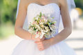 Bride with flowers in park wedding bouquet Stock Photos