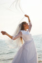 Bride with flying veil happy is standing on the beach and holding her Royalty Free Stock Photo