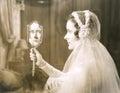 Bride gazing into hand mirror