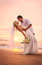 Bride and groom on beach at sunset a married couple a beautiful tropical Royalty Free Stock Photography