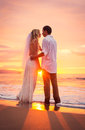 Bride and groom on beach at sunset a married couple a beautiful tropical Stock Photography