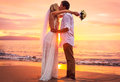 Bride and groom on beach at sunset a married couple a beautiful tropical Stock Photos
