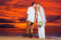 Bride and groom on beach at sunset a married couple a beautiful tropical Royalty Free Stock Image