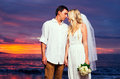 Bride and groom on beach at sunset a married couple a beautiful tropical Royalty Free Stock Photos