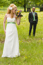 Bride and groom beautiful standing on a green meadow Stock Image