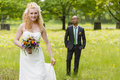 Bride and groom beautiful standing on a green meadow Royalty Free Stock Image